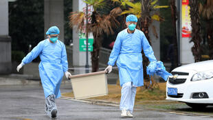 Medical staff carry a box as they walk at the Jinyintan hospital, where the patients with pneumonia caused by the new strain of coronavirus are being treated, in Wuhan, Hubei province, China, on January 10, 2020.
