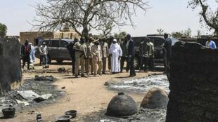 Le président malien, Ibrahim Boubacar Keïta, le 25 mars 2019, regardant des cases détruites lors du massacre du village peul d'Ogassogou.