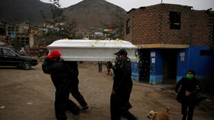 Funeral workers carry a coffin holding the body of a coronavirus disease (COVID-19) victim, at a cemetery, in Lima, Peru June 18, 2020.