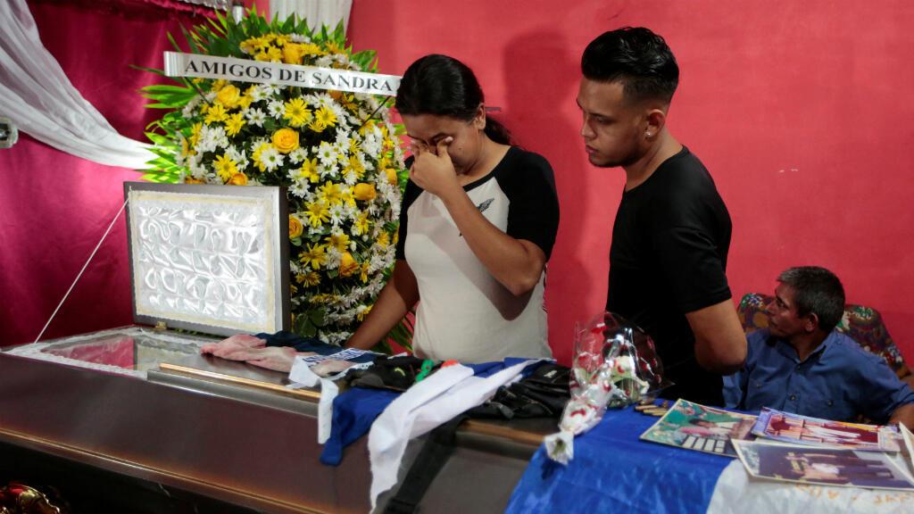 Familiares miran hacia un ataúd que contiene el cuerpo de Gerald José Vásquez, que murió durante enfrentamientos con la policía antidisturbios en la Universidad Nacional Autónoma de Nicaragua (UNAN), en Managua, Nicaragua el 14 de julio de 2018.