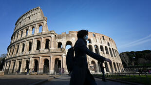 A tourist, wearing a respiratory mask as part of precautionary measures against the spread of the new COVID-19 coronavirus, walks past the closed Coliseum monument in Rome on March 10, 2020.