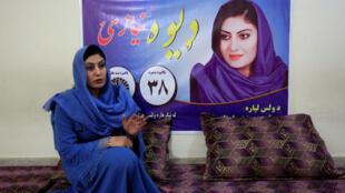 La candidata parlamentaria Dewa Niazai, frente a su afiche de campaña. 3 de octubre de 2018.