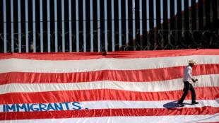 """Roberto Márquez, conocido como Roberz, camina sobre una gran bandera de EE. UU. como parte de una protesta llamada """"Estados Unidos de Inmigrantes"""", cuyo objetivo es exigir respeto a los migrantes, cerca de un muro fronterizo en El Paso, Texas, como se muestra en Ciudad Juárez, México, el 6 de junio de 2019."""