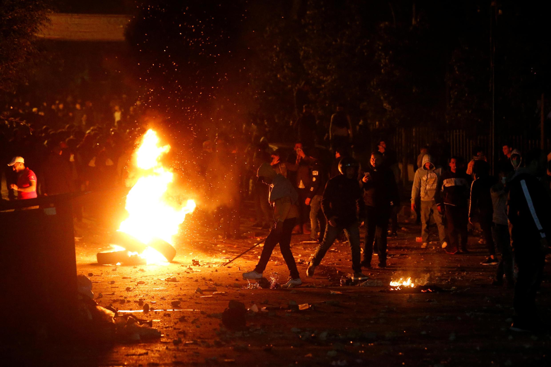 Los manifestantes se amontonan alrededor de una pila de neumáticos incendiados durante una protesta en la Corniche al Mazzraa en Beirut, Líbano, el 20 de diciembre de 2019.