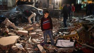 Des passants observent les dégâts provoqués par l'explosion d'une bombe dans un appartement du Caire, le 21 janvier 2016.