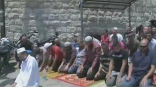 فلسطينيون يصلون أمام إحدى بوابات المسجد الأقصى 23 تموز/يوليو 2017