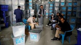 Trabajadores de la Comisión Electoral afgana abren las urnas y el material electoral en un almacén en Kabul, Afganistán, el 7 de octubre de 2019.