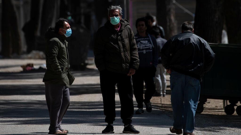 Los migrantes con máscaras faciales protectoras se encuentran a la entrada del campamento de Ritsona, luego de que las autoridades encontraron 20 casos de coronavirus y pusieron el campamento en cuarentena. Ritsona, Grecia, el 2 de abril de 2020.