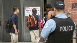 Un policier américain devant une école de Chicago, en août 2013.