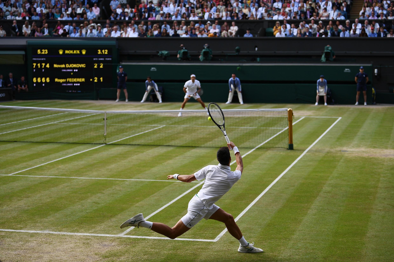 Le joueur de tennis serbe Novak Djokovic rend une balle au Suisse Roger Federer lors de la finale du dernier tournoi de Wimbledon le 14 juillet 2019 dans le sud-ouest de Londres