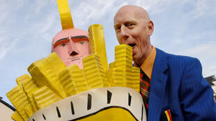 Belgian humorist Herr Seele poses next to the 'winning cornet' during a potato fries contest in Antwerp in 2006