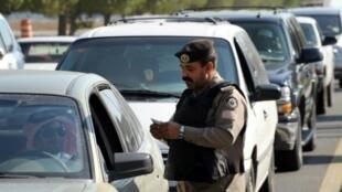 شرطي سعودي يدقق في بطاقة شخصية لمواطن في محافظة القطيف ذات الغالبية الشيعية