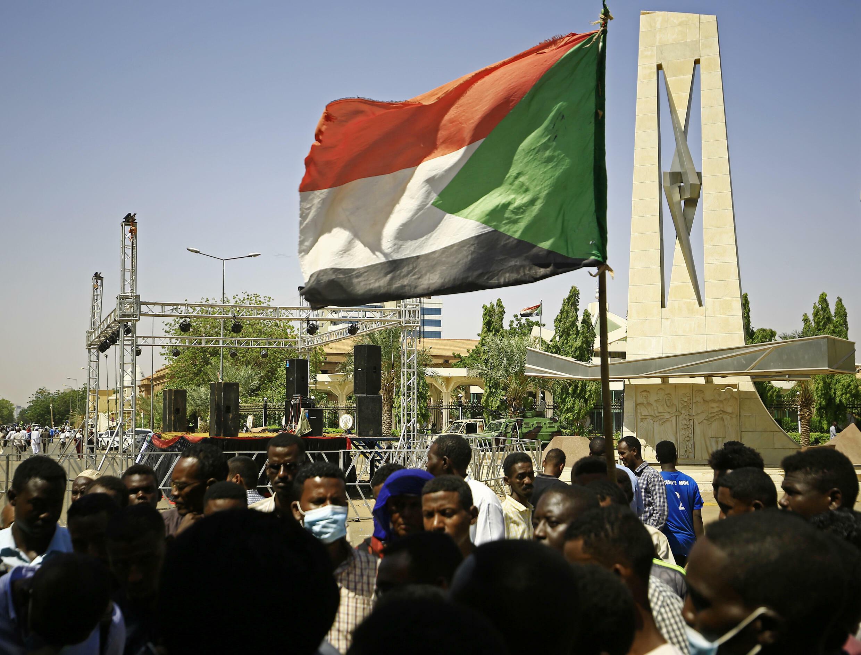 متظاهر يحمل العلم الوطني خلال اعتصام للمطالبة بحل الحكومة المؤقتة في السودان خارج القصر الرئاسي بوسط الخرطوم في 18 تشرين الأولف/أكتوبر 2021