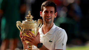 El serbio Novak Djokovic celebra con el trofeo después de ganar la final masculina individual contra el sudafricano Kevin Anderson en Londres, Inglaterra, el 15 de julio de 2018.