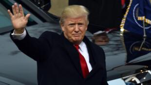 Le 45e président des États-Unis salue la foule alors qu'il s'apprête à entrer dans la Maison Blanche, vendredi 20 janvier.