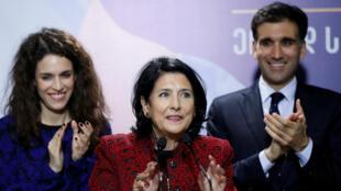 La candidata del partido Sueño Georgiano, ahora presidenta electa, Salome Zurabishvili (centro) acompañada de sus hijos durante una rueda de prensa en la sede de campaña de su partido en Tiflis, el 28 de noviembre de 2018.