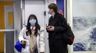 مسافران صينيان يرتديان كمامتين في مطار إيفالو في فينلندا. 24/01/2020