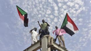 Des manifestants soudanais de la ville d'Atbara arrivent à la gare de Bahari à Khartoum pour célébrer la signature de l'accord de transition vers un pouvoir civil, le 17 août 2019.