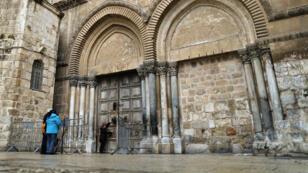 Des fidèles font face aux portes closes de l'église du Saint-Sépulcre, le 26 février 2018 à Jérusalem.
