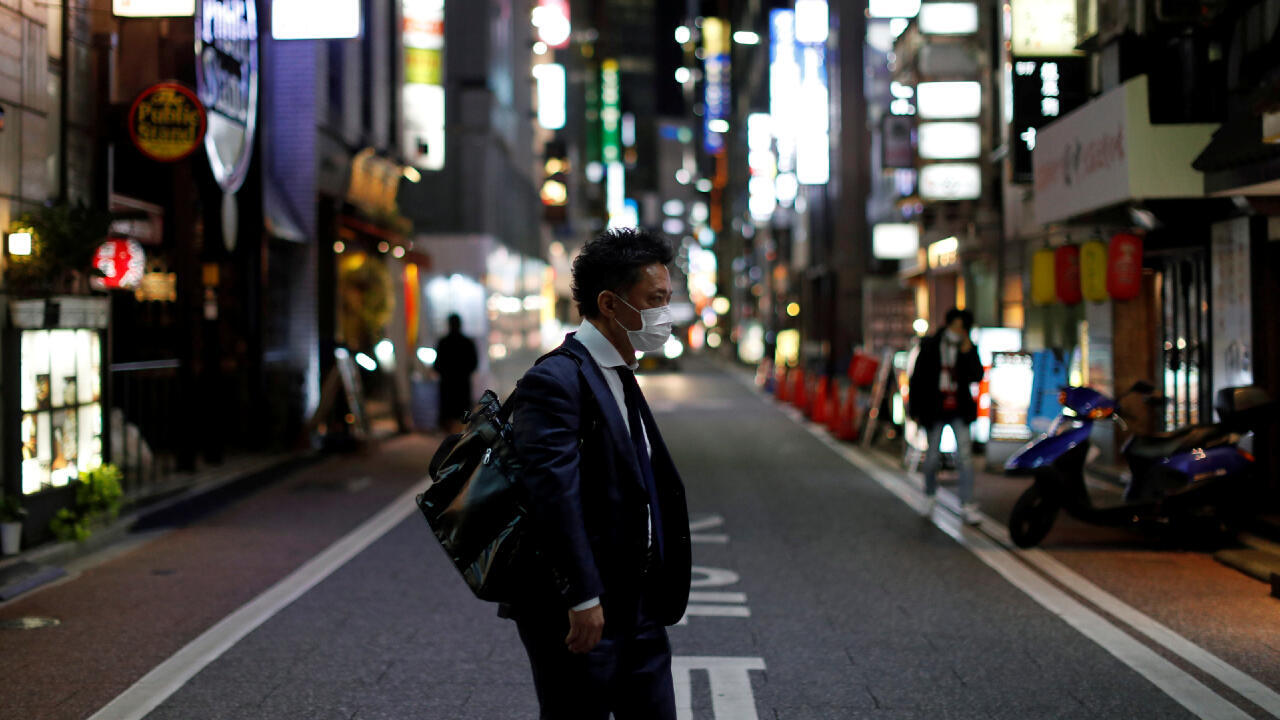 A man wearing a protective face mask, following an outbreak of the coronavirus disease (COVID-19), walks at Ginza shopping and amusement district in Tokyo, Japan April 2, 2020.