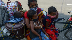 Unas familias de trabajadores migrantes viajan en un carro a sus loclidades de origen el 7 de mayo de 2020 en la ciudad india de Siliguri