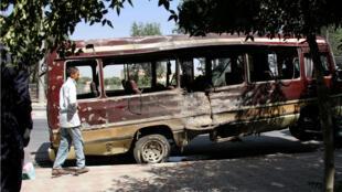 Un niño pasa junto a los restos de un autobús después de un atentado suicida en Kabul el 25 de julio de 2019.