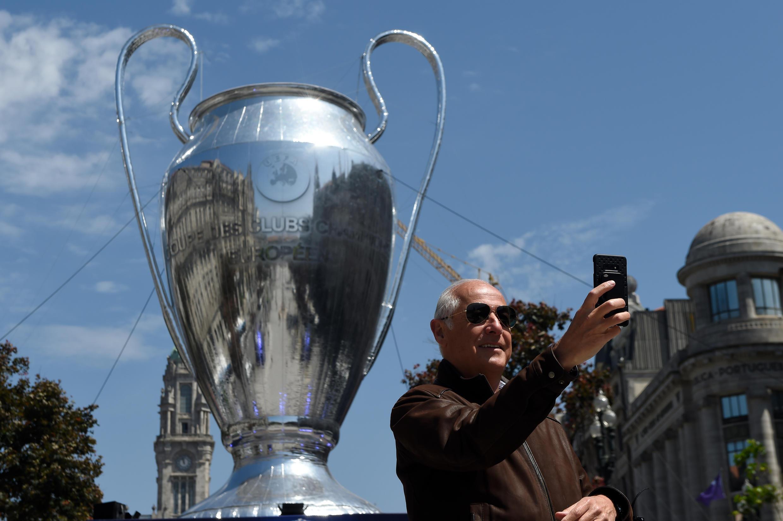 Un hombre se toma una foto ante una réplica hinchable de la Copa de Europa, el 28 de mayo de 2021 en Oporto