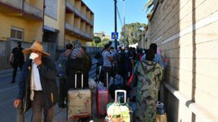 مواطنون مغاربة عالقون في جيب سبتة الإسباني مصطفون أمام الحافلة التي ستنقلهم إلى بلدهم، 22 أيار/مايو 2020