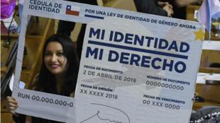 """La diputada Natalia Castillo, del partido Frente Amplio, sostiene una falsa tarjeta gigante de identidad chilena que dice """"Mi identidad, mi derecho"""", durante una sesión en el Congreso Nacional en Valparaíso, el 12 de septiembre de 2018."""