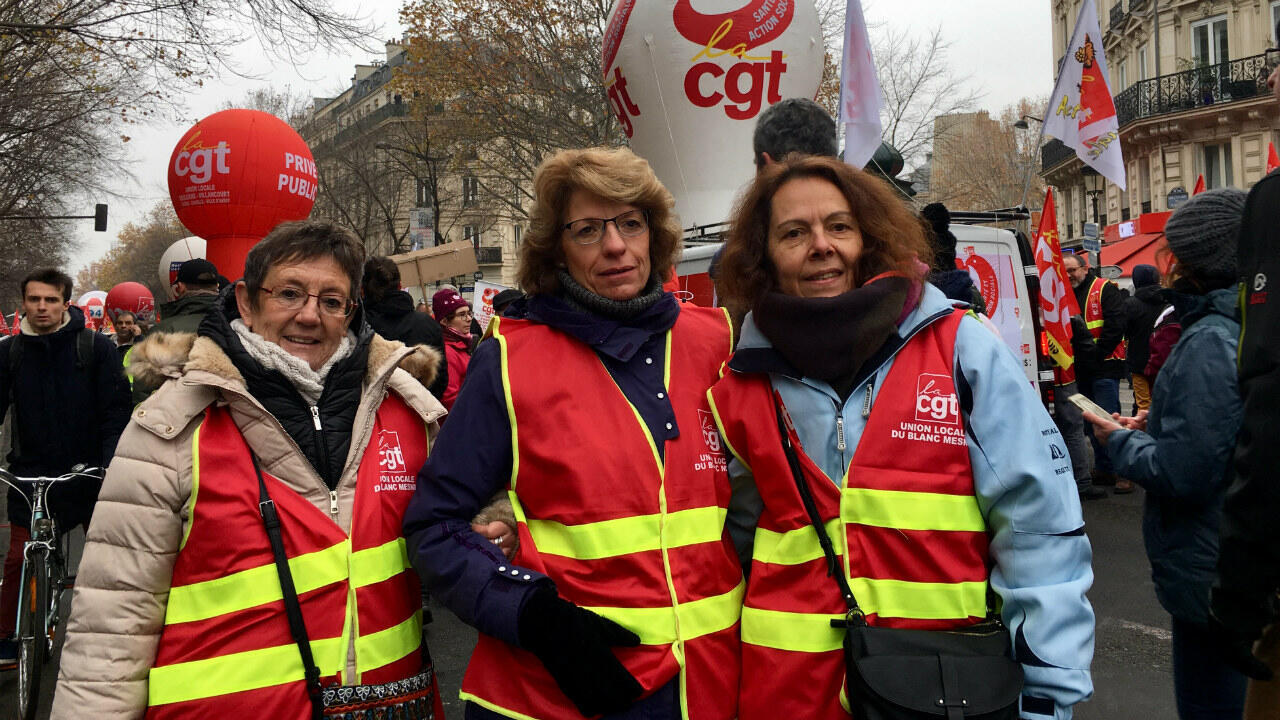 Protesters against French President Emmanuel Macron's proposed pension reform, including Valerie (R), a music teacher from Drancy, march in Paris on December 5, 2019.
