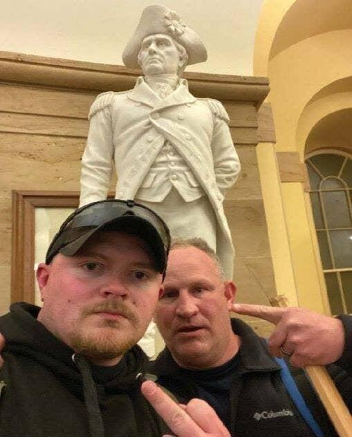 Jacob Fracker (left) and Thomas Robertson (right) pose for a selfie in front of a statue of John Stark, inside the US Capitol building.
