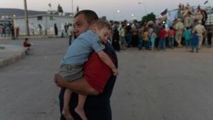 لاجئون سوريون عائدون من لبنان يتجمعون قرب شاحنة عسكرية سورية في ضواحي دمشق في 13 آب/أغسطس 2018