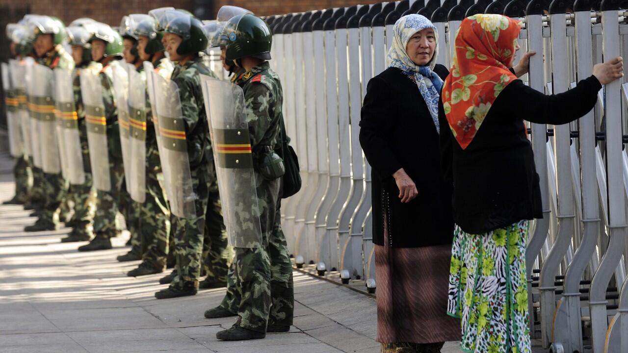 Mujeres de la etnia uigur miran a través de una valla de seguridad al Gran Bazar que permanece cerrado mientras los soldados chinos observan en Urumqi, en la región occidental de Xinjiang, China, en una imagen de archivo del 9 de julio de 2009.