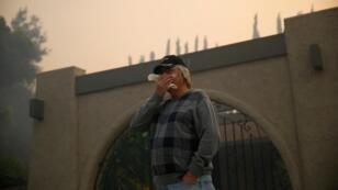 """Un homme regarde les pompiers lutter contre le """"Peak Fire"""" dans la vallée de Simi, en Californie, lundi 12 novembre 2018."""