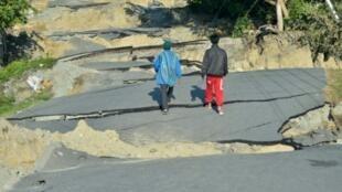Dos jóvenes caminan por una carretera destruida en Palu, este lunes 1 de octubre de 2018 en la isla indonesia de Célebes, golpeada tres días antes por un terremoto y un tsunami