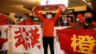This photo taken on April 18, 2020 shows fans of the Wuhan Zall football team welcoming the team members home at the railway station in Wuhan, in China's central Hubei province. - Wuhan Zall, the Chinese Super League team from the epicentre of the coronavirus pandemic, made an emotional return to the city after more than three months torn from their families.