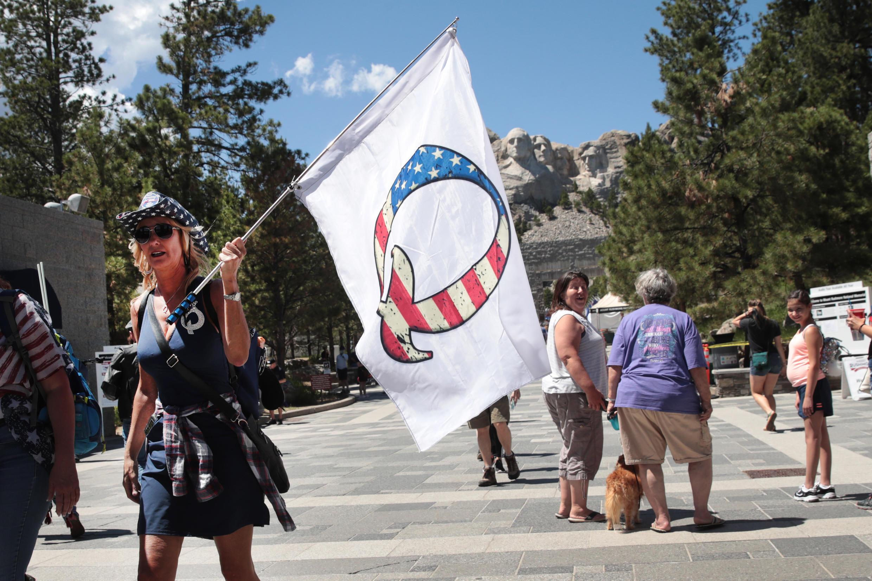 """Une supportrice de Donald Trump tient un drapeau à l'effigie de la mouvance """"QAnon"""", le 1er juillet 2020 au mont Rushmore, dans le Dakota du Sud."""