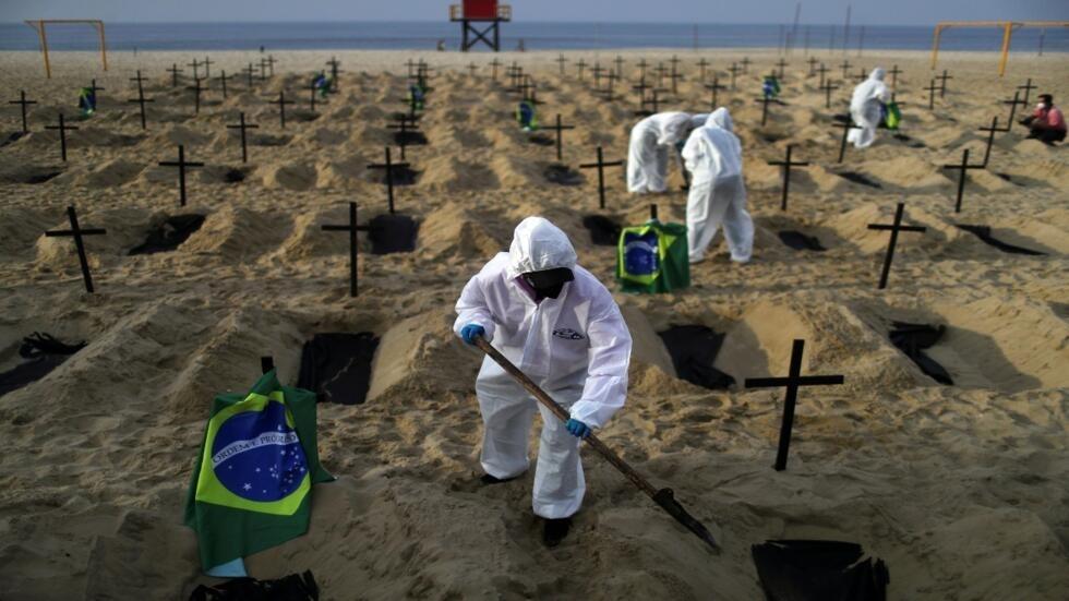 Activistas de la ONG Río de Paz, con equipo de protección, cavan tumbas en la playa de Copacabana simbolizando a los muertos por la Covid-19, durante una manifestación en Río de Janeiro, Brasil, 11 de junio de 2020.