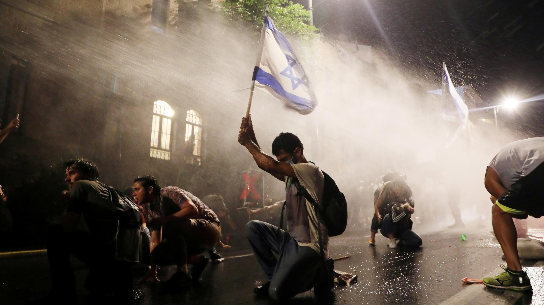 La policía usa cañones de agua mientras los israelíes protestan contra el primer ministro Benjamin Netanyahu en Jerusalén el 18 de julio de 2020.