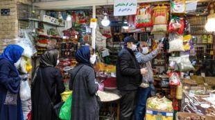 زبائن يضعون كمامات في أثناء تبضعهم من محل في بازار تاجريش بطهران، 25 نيسان/ابريل 2020، أول أيام رمضان في البلاد.