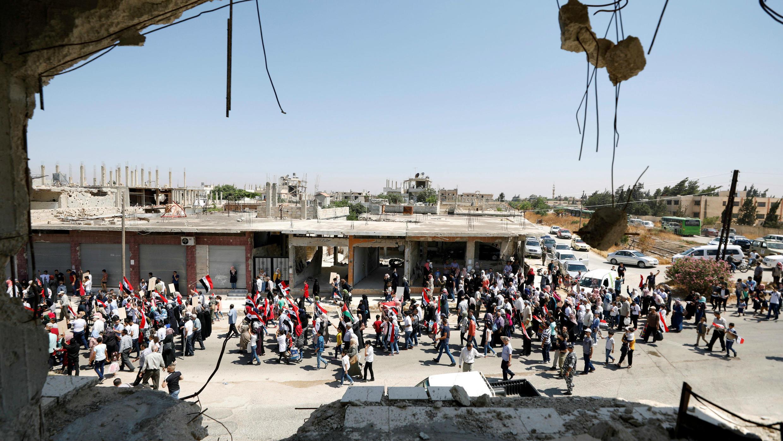 Los retornados caminan juntos y sostienen banderas sirias al entrar en la ciudad de Qusayr, Siria, el 7 de julio de 2019.