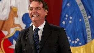 Brazil's President Jair Bolsonaro laughs during a joint press conference with Chilean President Sebastian Pinera (out frame) at La Moneda Presidential Palace in Santiago, on March 23, 2019.