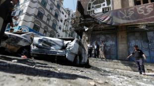 Personas observan vehículos dañados en una calle donde los combatientes hutíes se enfrentaron recientemente con las fuerzas del expresidente de Yemen, Alí Abdalá Saleh, en Saná, el 5 de noviembre de 2017.