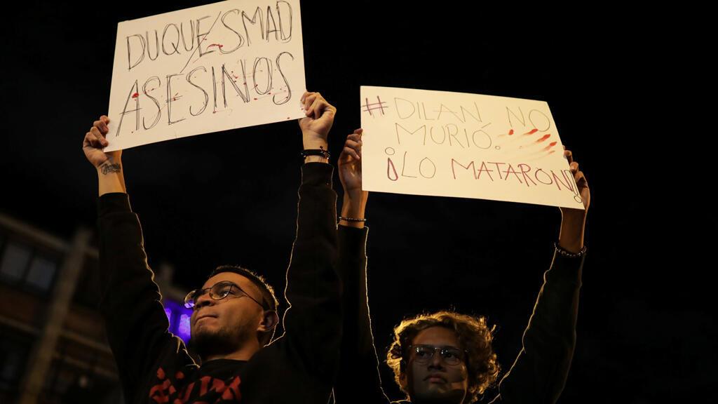 Manifestantes sostienen pancartas que reclaman por la muerte del estudiante Dilan Cruz mientras la gente se congregaba frente al hospital de San Ignacio, donde el joven manifestante fue herido de muerte por el escuadrón especial antidisturbios (ESMAD) en Bogotá, Colombia, el 25 de noviembre de 2019.