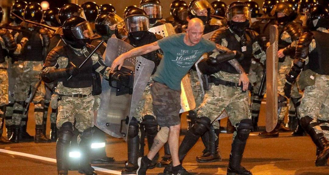 Agentes encargados de hacer cumplir la ley detienen a un hombre durante los enfrentamientos con partidarios de la oposición después de que se cerraran las urnas en las elecciones presidenciales en Minsk.