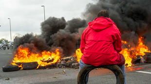 A protesting sailor sits near burning tires blocking access to the Channel Tunnel.