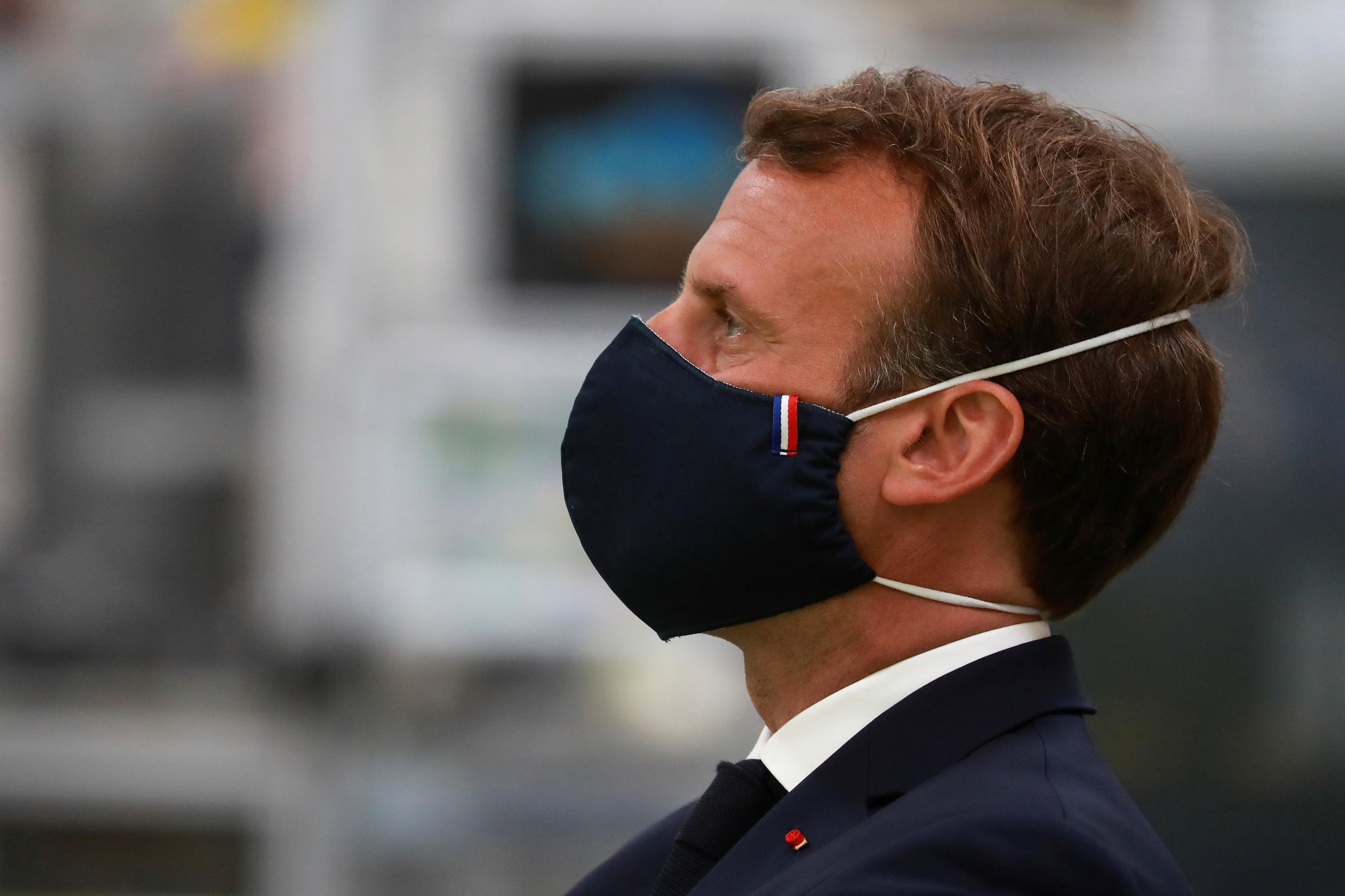 French President Emmanuel Macron, wearing a protective mask, looks on as he visits a factory of manufacturer Valéo in Etaples, near Le Touquet, France May 26, 2020.