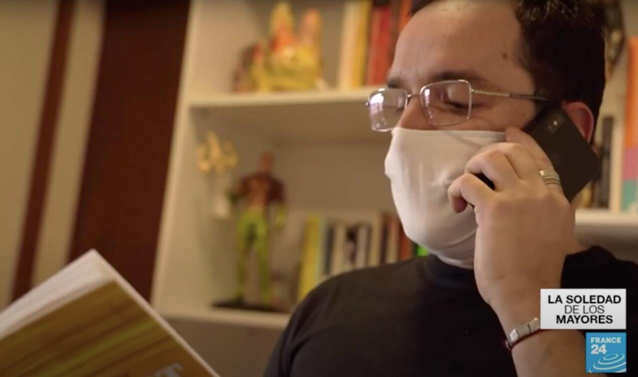 Eduardo Maciel mientras lee un poema por teléfono a un anciano en medio de la pandemia en Brasil.