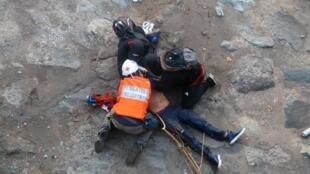 Equipos de emergencia trasladan a un manifestante que se encuentra inconsciente, luego de caer en el río Mapocho, durante las protestas en contra del Gobierno de Sebastián Piñera, este viernes 3 de octubre, en Santiago, Chile.