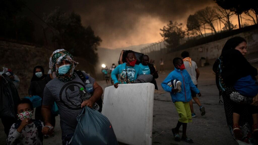 Refugiados y migrantes que llevan sus pertenencias huyen de un incendio que arde en el campamento de Moria en la isla de Lesbos, Grecia, el 9 de septiembre de 2020.